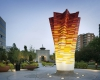 The design showcases the eye-catching Transformed Flower sculpture for visitors and passersby.