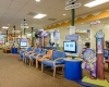 The waiting area includes interactive technology stations and three-dimensional graphic elements to create an inviting environment for children and families.