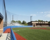 Field-level view of home plate area, home dugout/locker room and bleachers